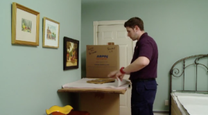 Arpin of RI packer in a bedroom carefully wrapping framed pictures