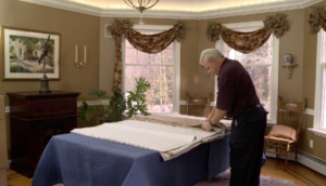 Arpin of RI packer in dining room spreading out export wrapping g paper on to the dining room table.