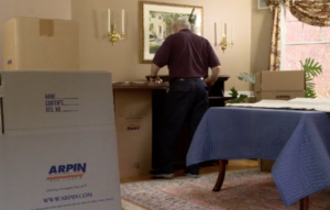 Arpin of RI packer in dining room carefully wrapping fragile items