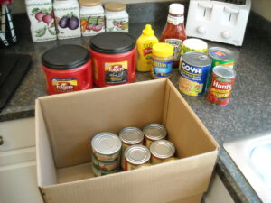 Arpin of RI 1.5 box in a kitchen partially filled with canned goods