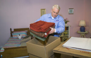 Arpin of RI packer standing in a bed room packing towels into a 3 cube carton