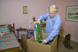 Arpin of RI packer standing in a child's bed room carefully packing board games into a 4.5 cube box