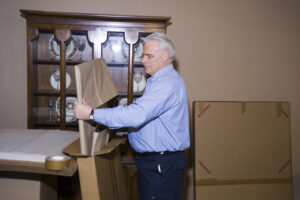 Arpin of RI packer standing in a dining room carefully packing a wrapped framed picture into a mirror carton