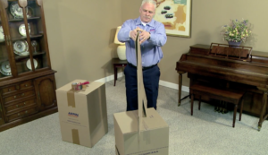 Arpin of RI packer standing in a dining room getting ready to tape up a carton