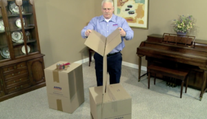 Arpin of RI packer standing in a dining room folding over the top flaps of a carton with care