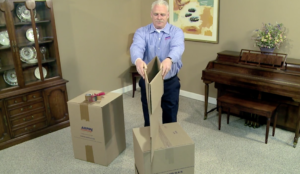 Arpin of RI packer standing in a dining room carefully folding over the top flaps of a carton and getting ready to flip it over