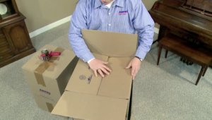 Arpin of RI packer standing in a dining room folding in the first two bottom flaps of a carton with precision