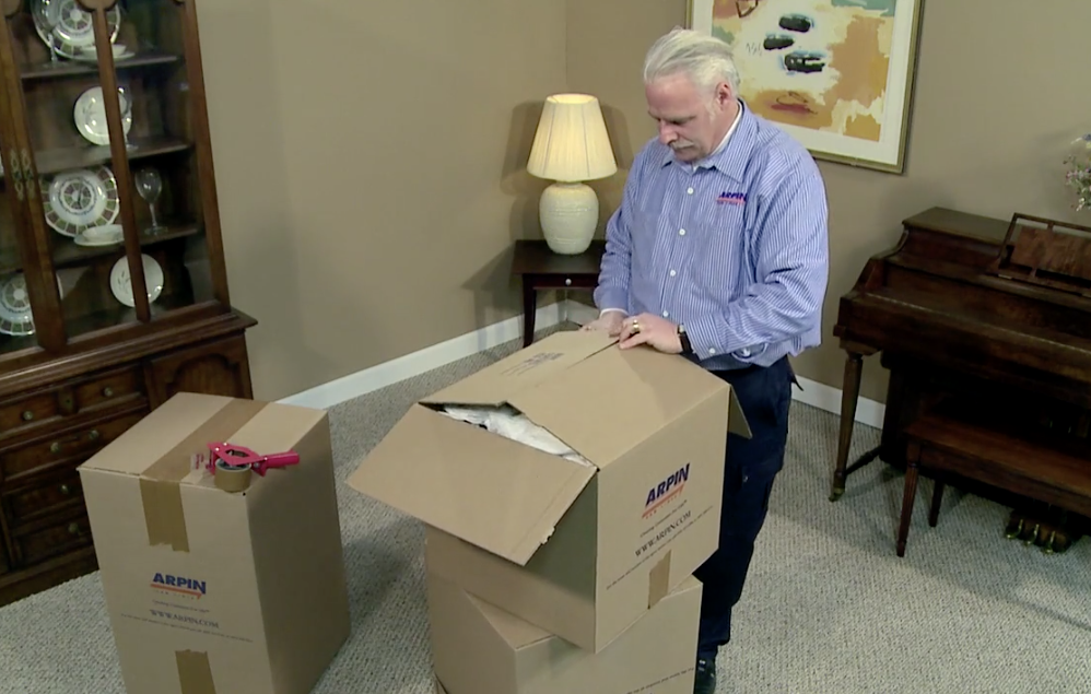 Arpin of RI packer standing in a dining room carefully folding in the first two top flaps of a fully packed carton
