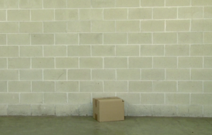An unlabeled carton sitting on the floor of a large warehouse