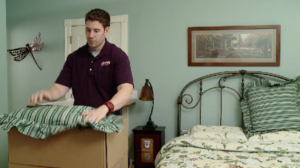 Arpin of RI packer in a bedroom packing up the last minute items of pillows and bedding