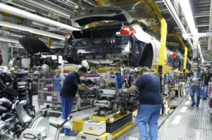 Image of workers assembling an automobile on an efficient assembly line in a car manufacturing plant