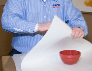 Arpin of RI packer in a dining room carefully wrapping a china bowl in paper