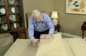 Arpin of RI packer in a dining room carefully wrapping a large cabinet speaker with export wrapping paper.