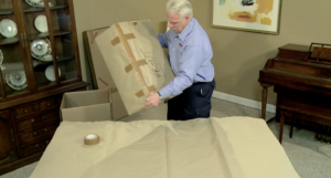 Arpin of RI packer in a dining room placing a fully wrapped cabinet speaker into a large carton.