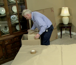 Arpin of RI packer in a dining room placing a fully wrapped cabinet speaker into a large carton with the delicate front against the side of the carton.