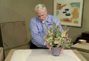 Arpin of RI packer in a dining room handling a fragile flower arrangement.