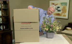 Arpin of RI packer in a dining room a fragile flower arrangement to ensure the flower arrangement fits into the carton