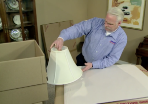 Arpin of RI packer in a living room placing a lampshade against the side of the cartons to ensure it will properly fit inside.