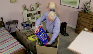 Arpin of RI packer in a bedroom placing board games into a 4.5 carton
