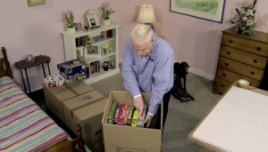 Arpin of RI packer in a bedroom placing the largest board games into a 4.5 carton