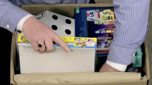 Arpin of RI packer in a bedroom placing smaller games into the upper layer of the carton.