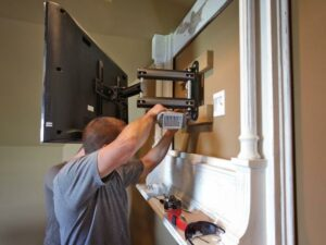 3rd party technician removing a flat-screen TV mount from the wall of a family room.