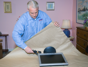 Arpin of RI packer in a bedroom wrapping a monitor in brown export wrap
