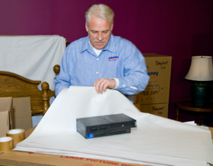 Arpin of RI packer in a bedroom wrapping the gaming system in white news paper.
