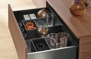 An open dresser drawer showing breakables inside.