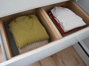 Image of an open dresser drawer showing folded clothing inside.