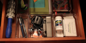 open dresser night stand drawer showing many smaller items inside.