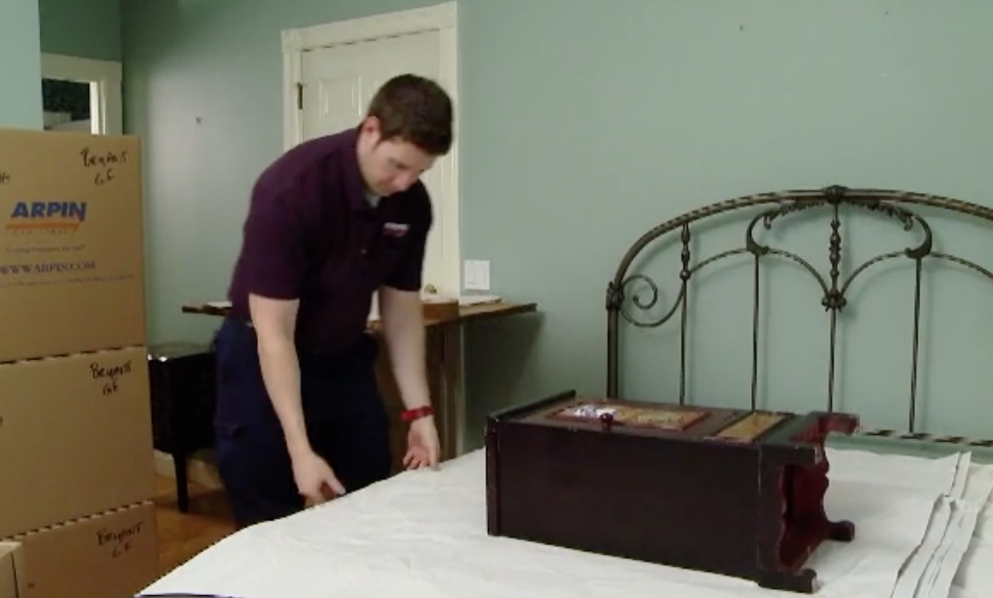 Arpin of RI packer packing a night stand with its drawer in a carton.