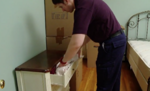 Arpin of RI packer stuffing a dresser drawer with paper to secure the contents.