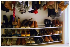 Image of a closet with neatly stacked shoes on the floor.