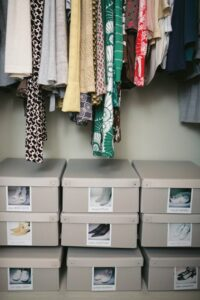 a closet with boxes of shoes stacked neatly on the floor.