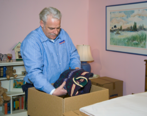 Arpin of RI packer in a bed room placing folded sweaters in a carton.