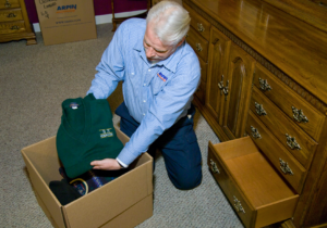 Arpin of RI packer in a bed room removing folded sweaters from a drawer and packing them in a carton.