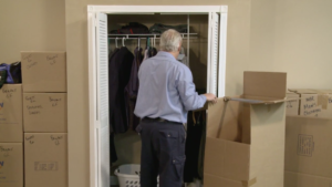 Arpin of RI packer in a bed room taking clothing out of a closet and packing them into a wardrobe carton