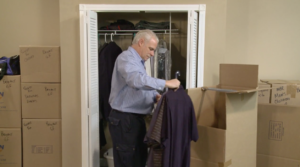 Arpin of RI packer in a bed room packing clothing into a wardrobe carton.