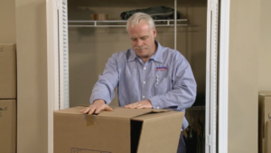 Arpin of RI packer in a bed room taping the top of a wardrobe carton.