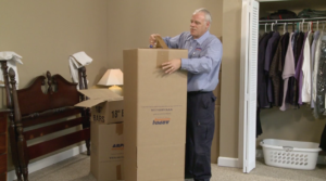 Arpin of RI packer in a bed room taping the bottom flaps of a wardrobe carton.