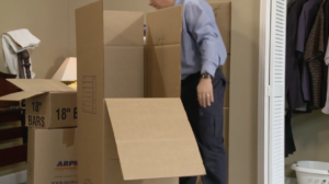 Arpin of RI packer in a bed room with a partially tapped wardrobe carton.