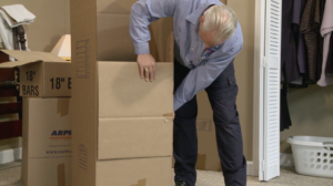 Arpin of RI packer in a bed room taping the front flaps of a wardrobe carton out of the way.