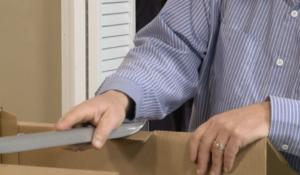 Arpin of RI packer in a bed room placing a wardrobe bar into the wardrobe carton.