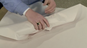 Arpin of RI packer in a dining room wrapping stemware by trapping air in the layers of paper.