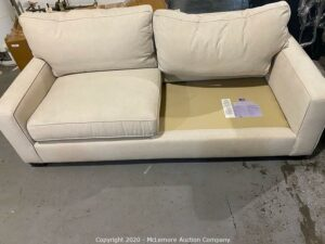 A white sofa missing a cushion which was lost during a move.