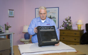 Arpin of RI packer in a bedroom getting ready to pack a small electric guitar amplifier into a carton.