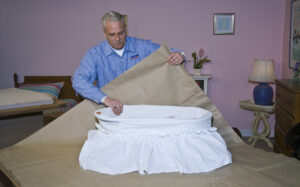 Arpin of RI packer in a bedroom carefully wrapping a white baby bassinette with export paper before packing it into into a carton.