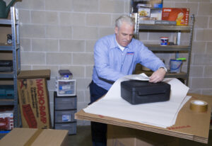 Arpin of RI packer in a basement wrapping a small plastic strong box into a carton.