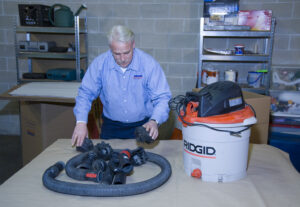 Arpin of RI packer in a basement packing the attachments of a shop vacuum into a carton so they are not misplaced during the move.